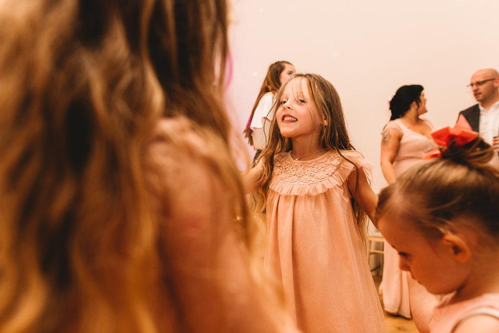 Flower girls have fun dancing at rustic wedding