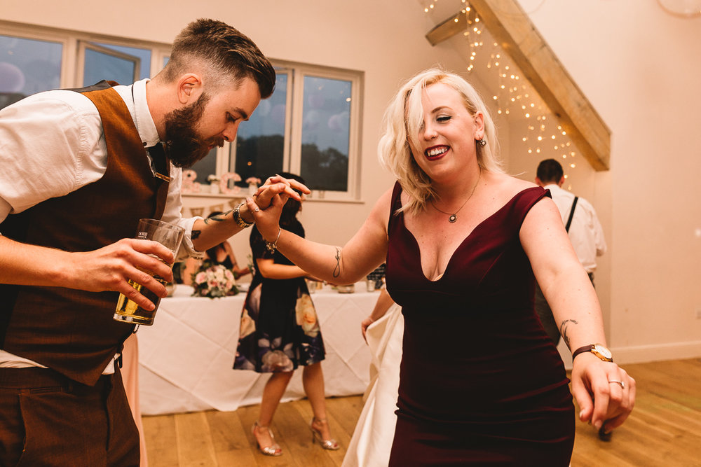 Alternative couple with tattoos dance at fun wedding party