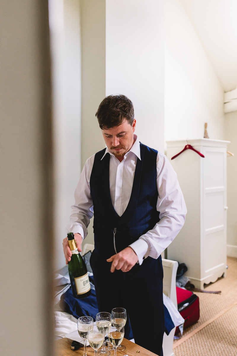 Fun groom prep drinking champagne at chateau wedding