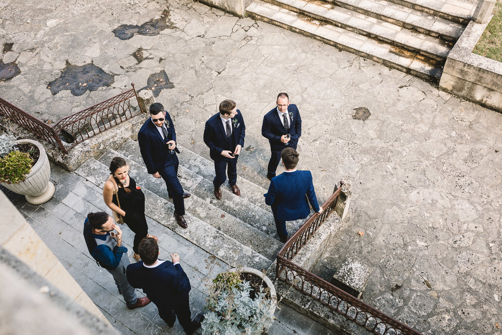 Groomsmen in blue suits on chateau terrace at france destination wedding
