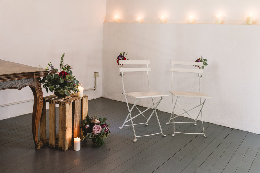 Rustic candles, flowers and crates in ceremony barn | France Destination Wedding