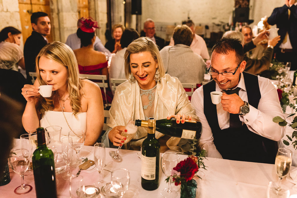 Fun guests drinking champagne at rustic france chateau wedding