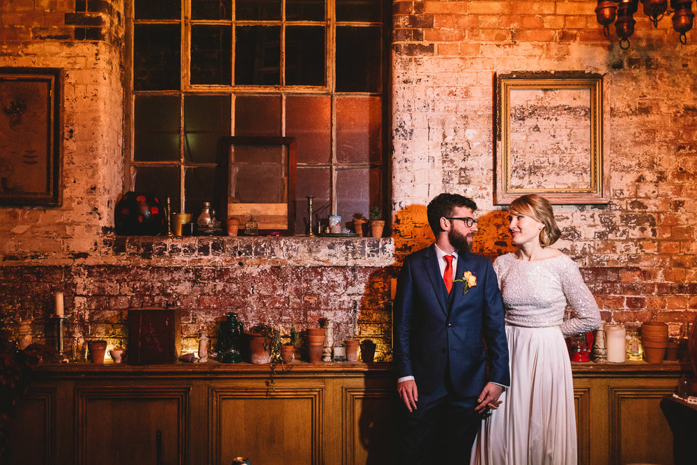 Wedding photo at Clapton Country club a cool industrial wedding venue in Hackney. A bride and groom are stood side by side holding hands naturally. The bride wears a two piece wedding dress, with the long sleeved crop top with cream sequins giving a glitter effect she has short blonde hair. The groom has glasses and a big beard and is wearing a ted baker blue suit with fun orange tie. The backdrop is in the opium room in the london wedding venue, with lots of industrial rustic brick work, a big blacked out window and potted plants and trinkets scattered about.
