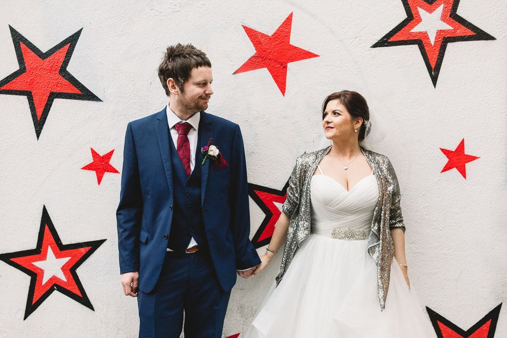 Wedding photo of bride and groom taken by warwickshire wedding photographer kate jackson. The couple are stood against a white wall covered in red and black graffiti of stars. They are holding hands, the bride is wearing a silver sparkle sequin glitter jacket and white wedding dress, and the groom wears a navy three piece suit and red tie. He is a bearded groom.