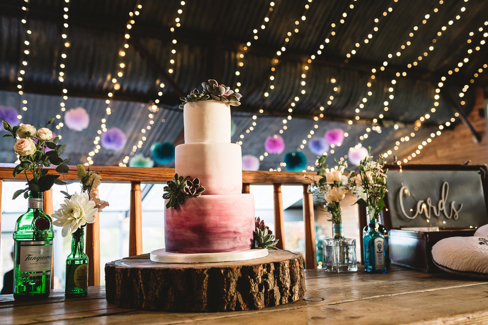 Ombre purple and white three tired wedding cake, with succulents on it. It sits on a rustic wood log piece and is surrounded by quirky gin bottles filled with flowers. Behind it there is the sloping metal barn roof  Stone Barn in the Cotswolds, it is covered in fairy lights and has colourful poms hanging from it.