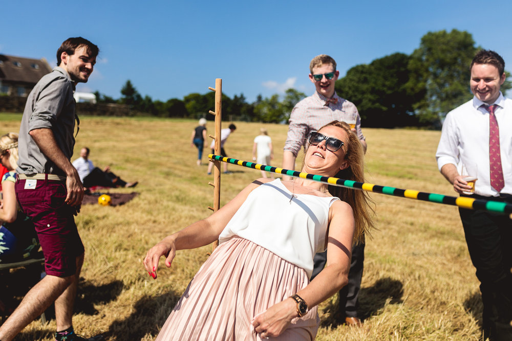 A woman is wearing a white top and silk pink pleated skirt and sunglasses and is playing a fun wedding game of limbo in a field at an outdoor festival wedding in Sheffield. She is surrounded by three other wedding guests with pints of beer waiting their turn and laughing.