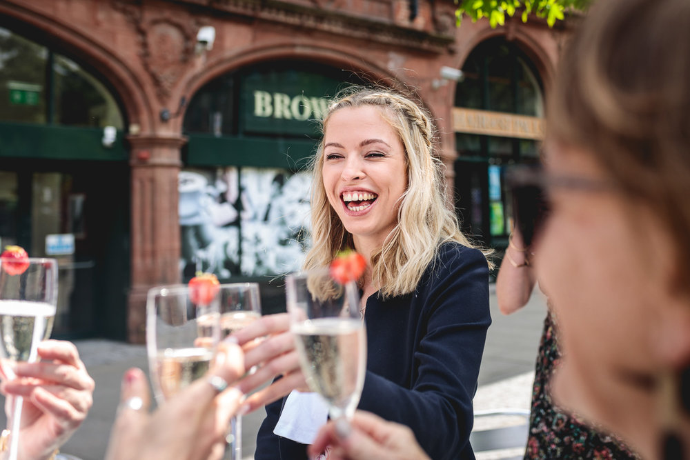 Fun laughter from wedding guest with blonde hair wearing floral dress, whilst doing a cheers with prosecco and strawberries in Sheffield town