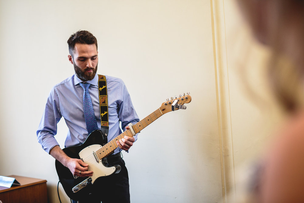 Groomsmen playing guitar during ceremony at sheffield town hall