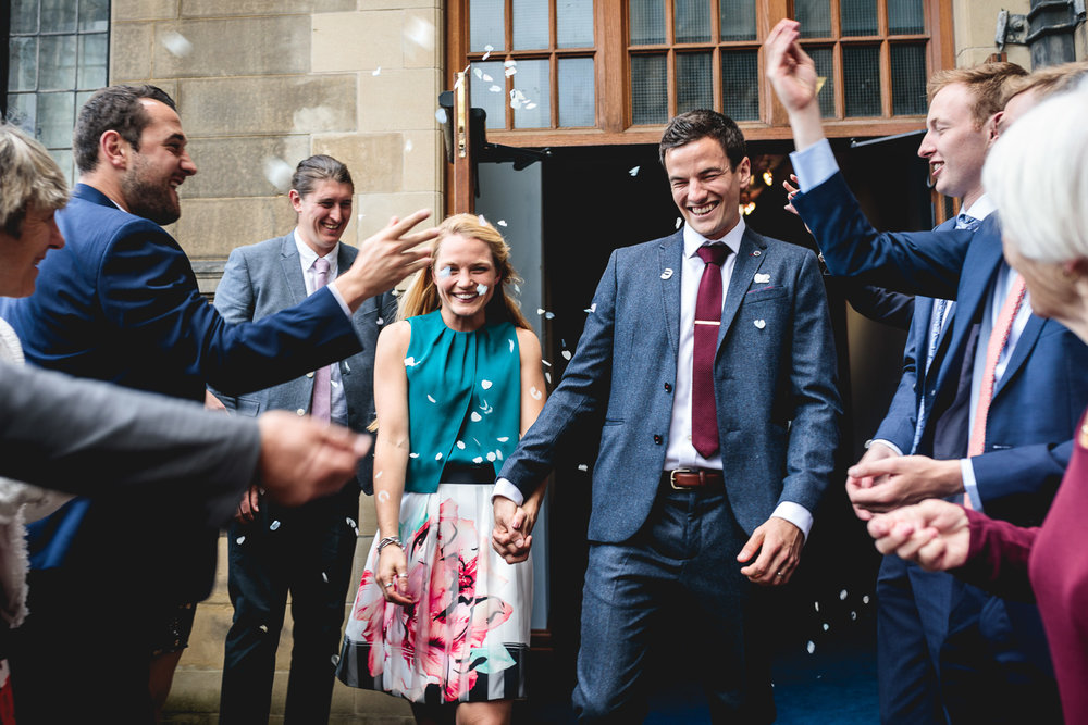 Couple walk out to fun white biodegradable confetti throw at Sheffield Town Hall Wedding