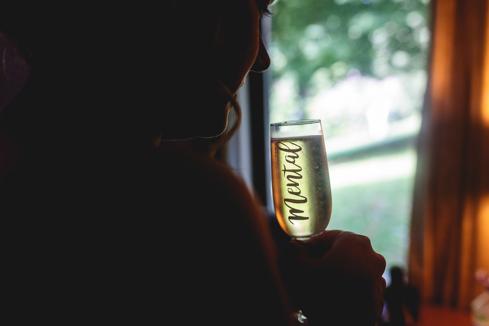 Bridesmaid sips prosecco from fun glass that says mental whilst getting ready for a festival wedding in sheffield
