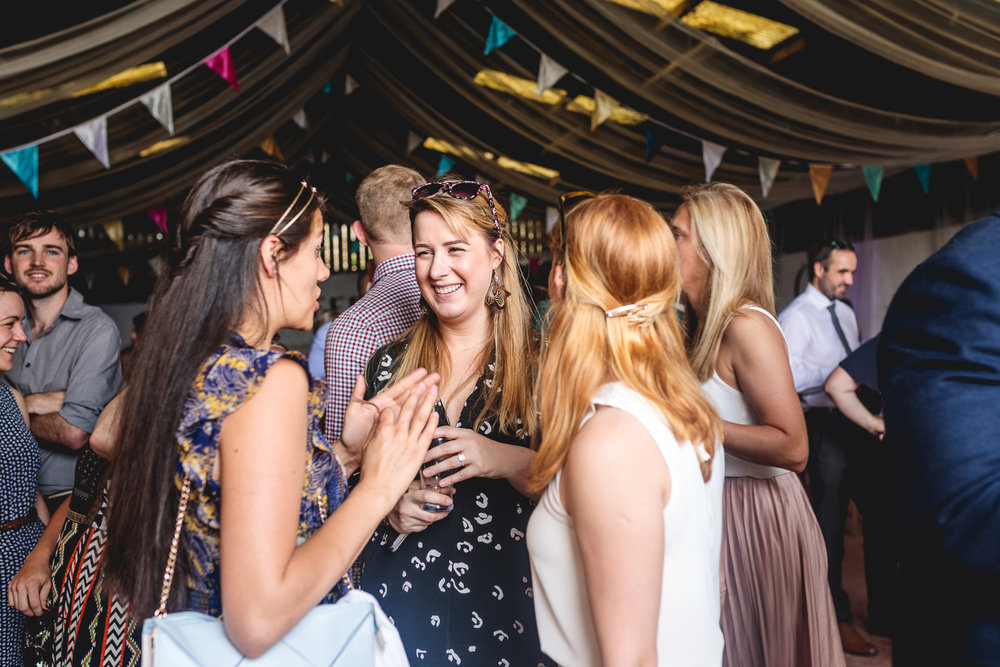 Guests in barn having fun standing and laughing, stood under colourful bunting at Festival wedding in sheffield