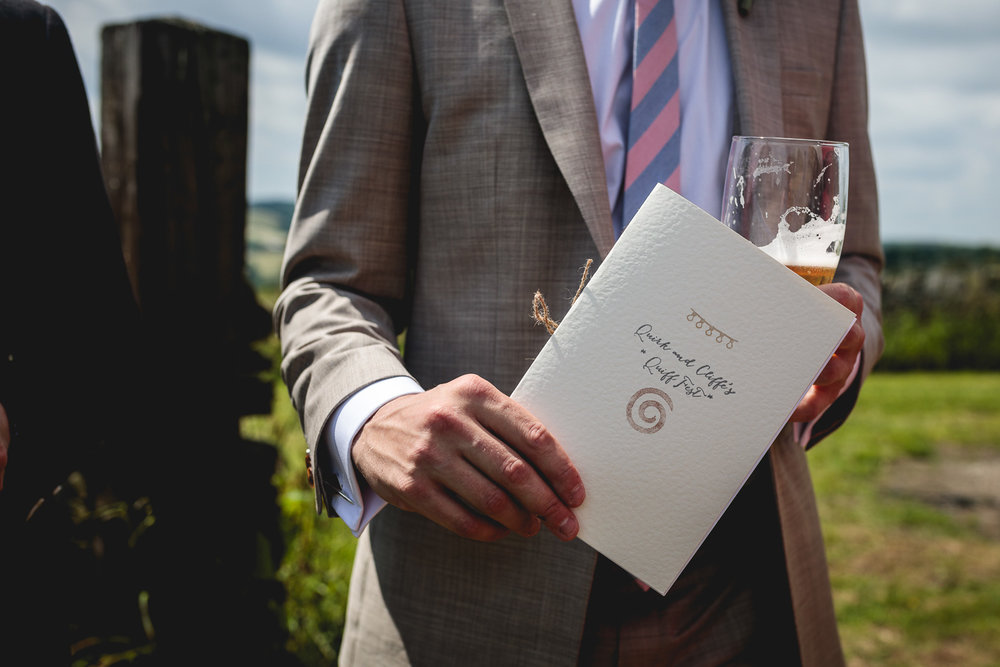 Guest holds DIY festival wedding order of service in outdoor field in sheffield