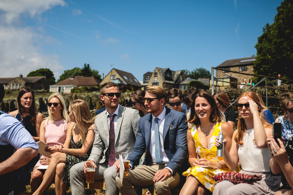 Guests sat in field in Sheffield awaiting the ceremony at festival wedding
