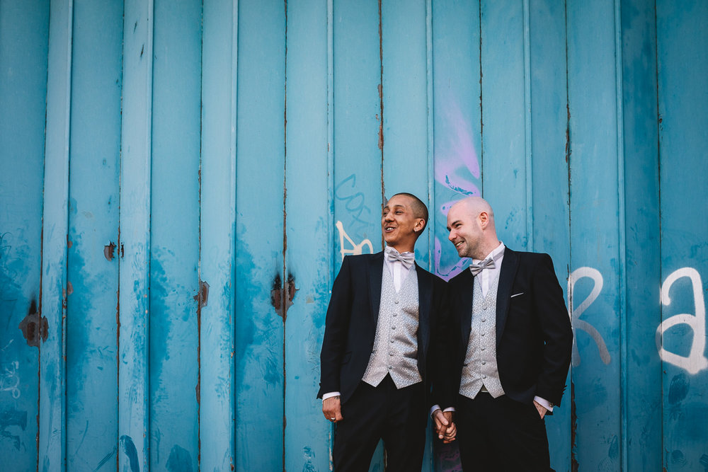 Two men on their wedding day in funky silver and black tux's laughing in front of colourful blue shutters at Bond Company Wedding in Birmingham