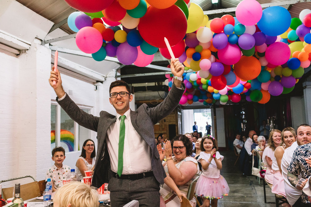 Man holding up candles like Lumiere in beauty and the beast during fun wedding in Hackney. There are hundreds of colourful balloons in an arrangement like Disney's up on the roof