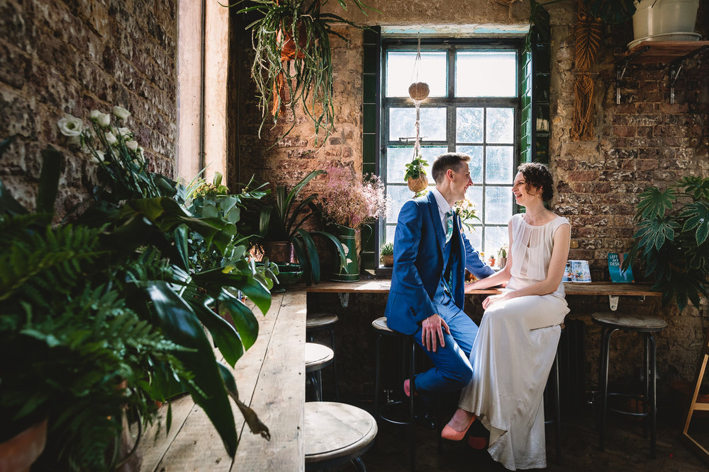 London couple sat on stools smiling at each other in Clapton Tram Store surrounded by urban bricks and colourful green plants | London Wedding Photography