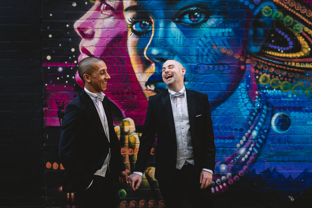 Same sex wedding at the Bond Company in Digbeth. Two grooms are holding hands and having fun laughing in front of alternative colourful graffiti wall at the Custard Factory