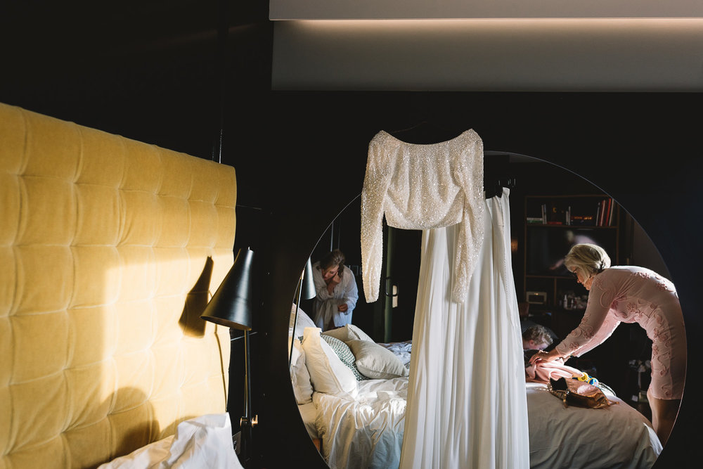Photo of two piece wedding dress hanging by mirror in London
