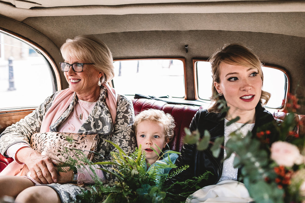 Bride and bridal party in wedding car on way to Hackney Town Hall