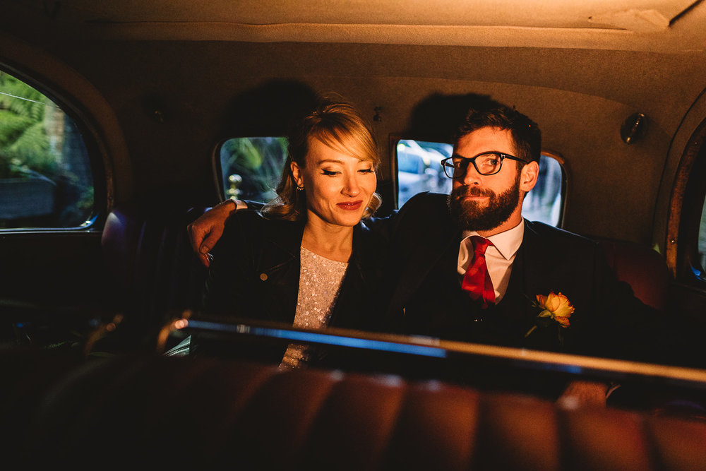 Bride and beared groom wearing glasses sitting together on the backseat of vintage car, lit  with a video light giving a street lamp like effect at a East London wedding.