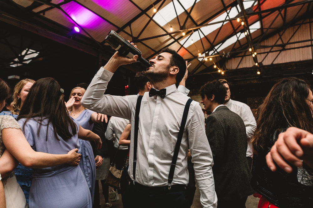 Man with beard drinking from a bottle of red wine at warehouse wedding in sheffield-1.jpg