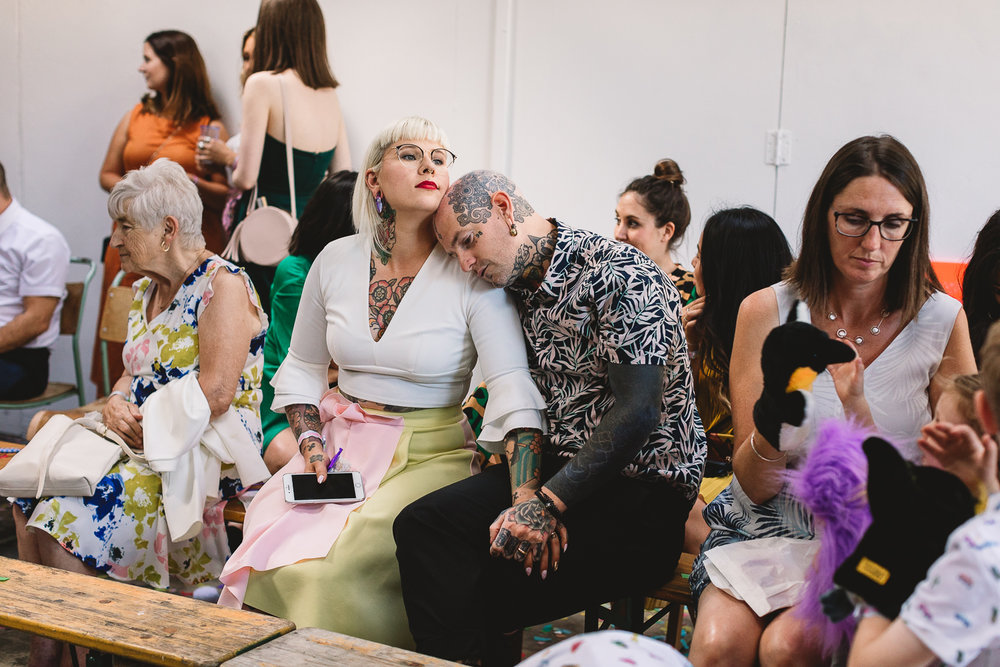 Tattooed couple sitting in a crowded room holding hands at hackney wedding venue. The man  has face tattoos and piercings and is resting his head on the bridesmaid who has arm and check tattoos, short blond hair and is wearing red lipstick, a white top and pink and yellow block skirt.