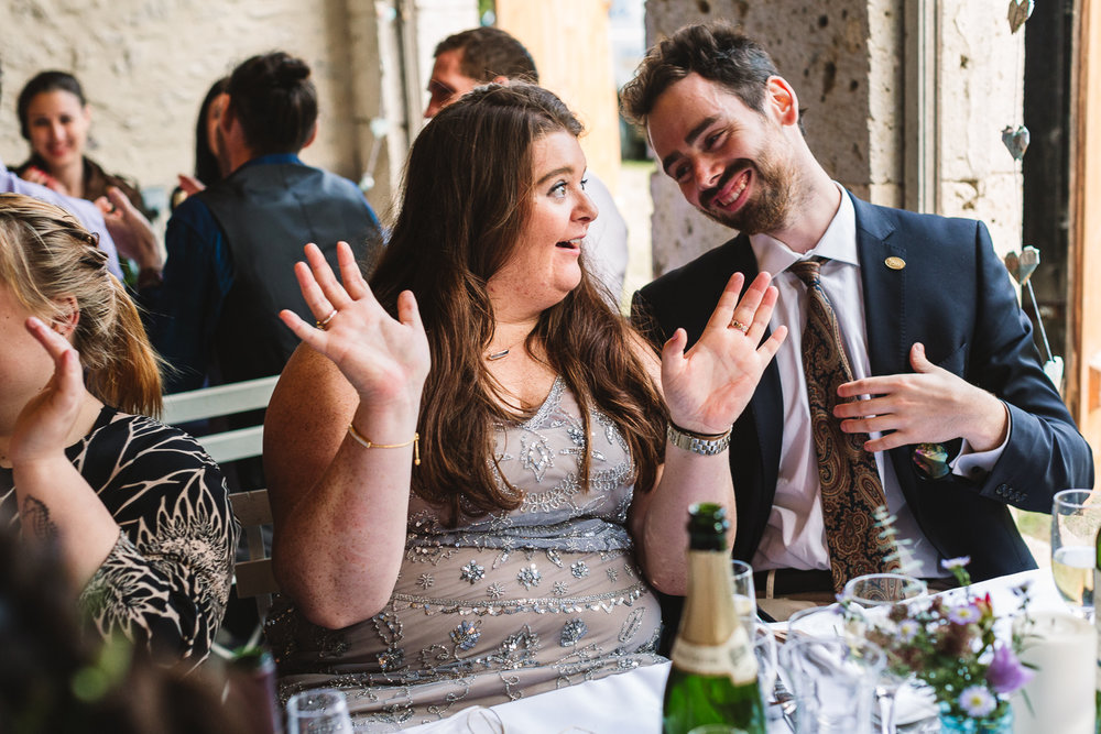 Wedding guest doing fun hand gesture like 'ta-daaaa' at France Chateau wedding-1.jpg