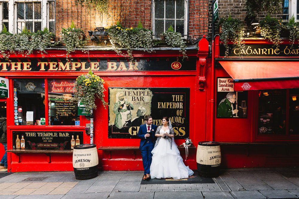 Bride and Groom having a pint outside of a pub on their wedding day.