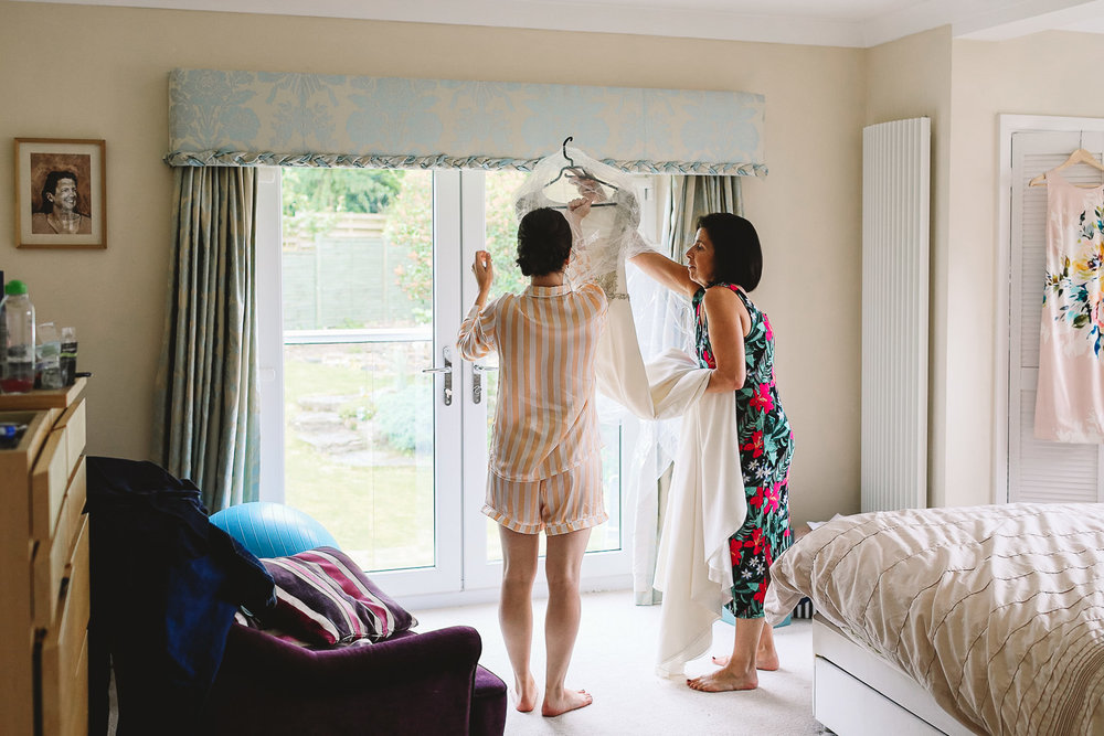 Bride and mother hang Rosa Clara wedding dress in window during relaxing wedding preparations in Sheffield