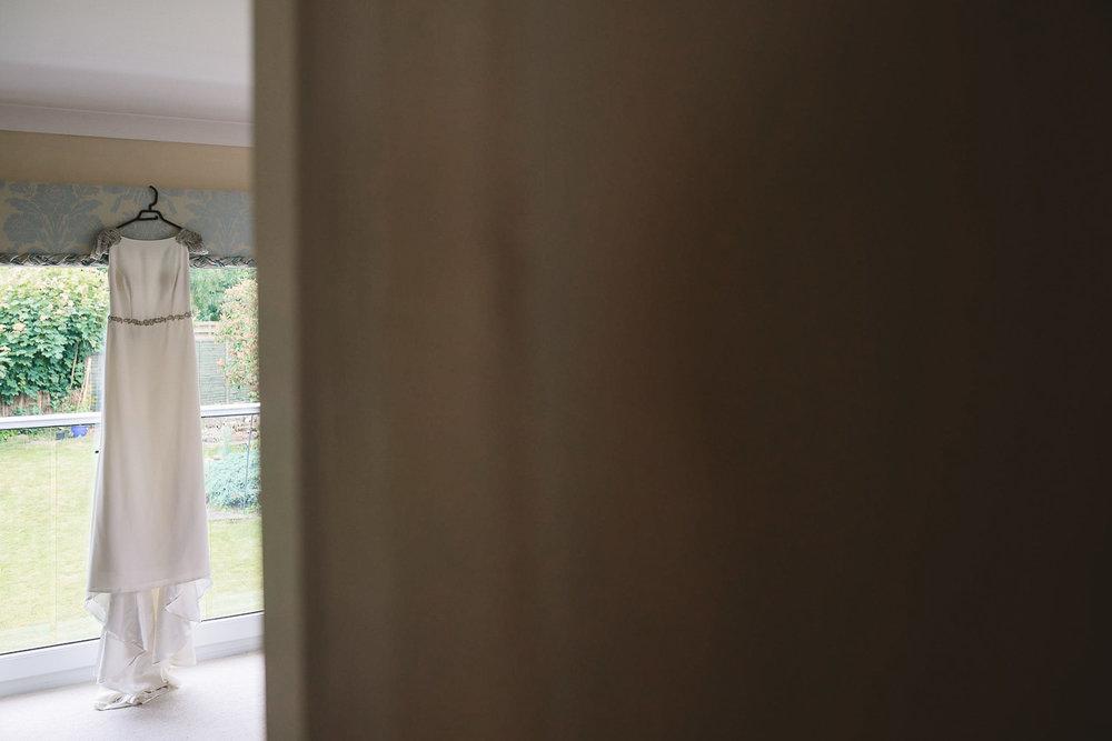 Photo of classic white Rosa Clara wedding dress hanging in window at Sheffield wedding
