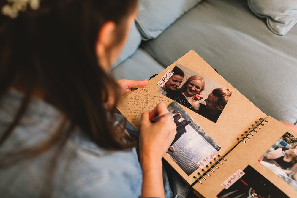 Photo of bridesmaid writing a message to bride in book with photos of them during bridal prep at Sheffield wedding