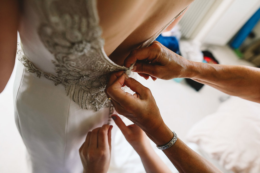 Close up of brides mum and sisters hands doing brides rosa clara wedding dress up with amazing bead detail on the dress at relaxed Sheffield Wedding