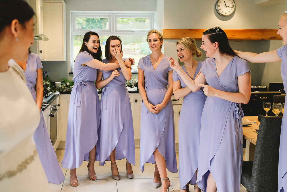 Bridesmaids in lilac & other stories dresses see bride for the first time and cry and laugh at the same time during bridal prep in Sheffield