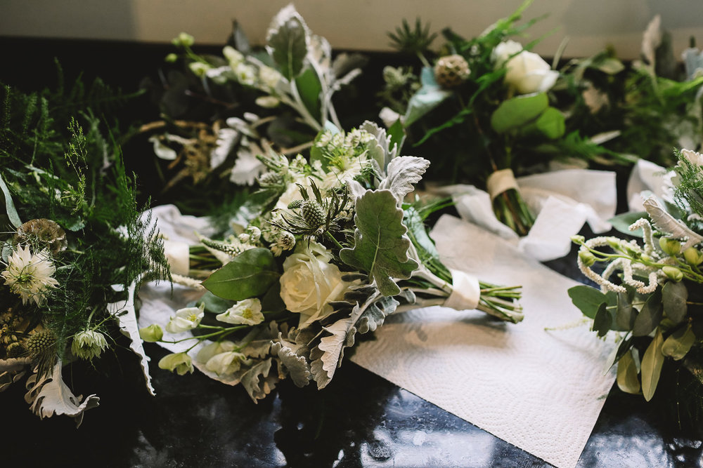 Photo of bridesmaid bouquets with roses and green foliage drying on the side at relaxed Sheffield wedding