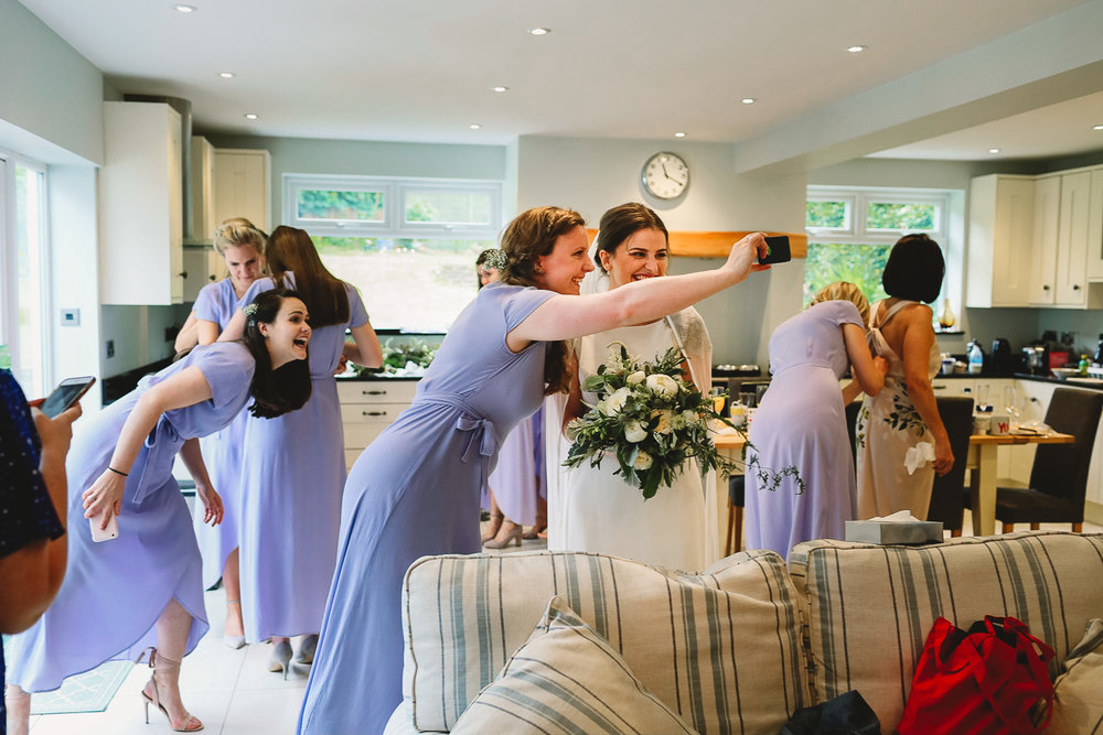 Bridesmaid taking selfie with the bride and another bridesmaid photobombing and pulling funny face in the background at fun Sheffield wedding
