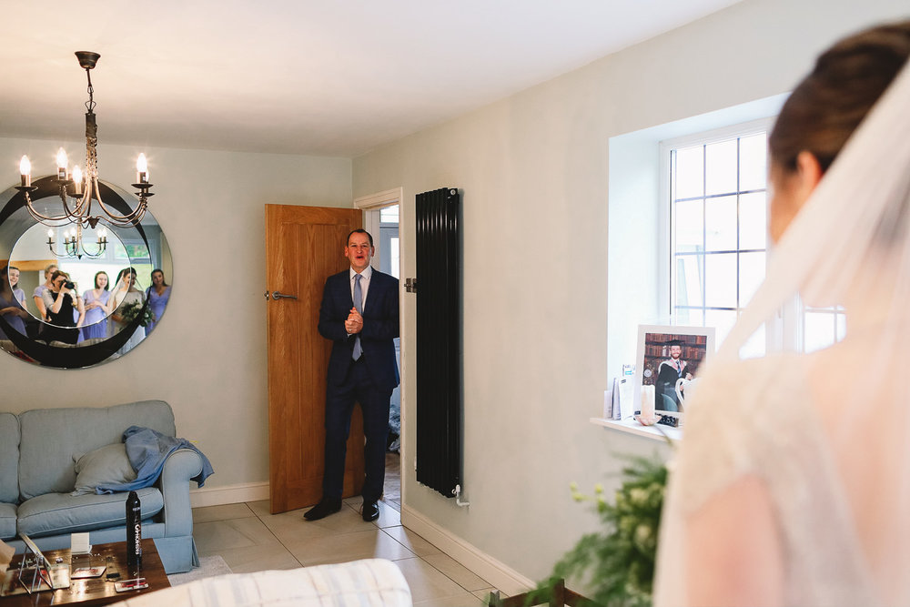 Dad sees bride for the first time and has the most happy and emotional look on his face as he walks in the room at relaxed Sheffield wedding