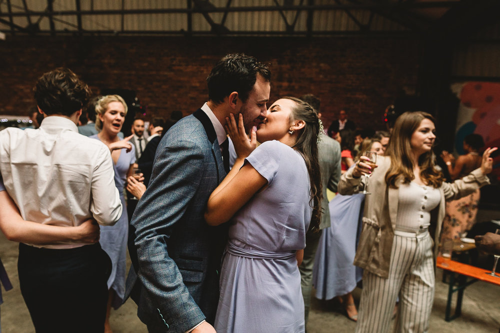 Bridesmaid in lilac dress kissing a man in a cool blue suit at alternative warehouse wedding venue 92 burton road