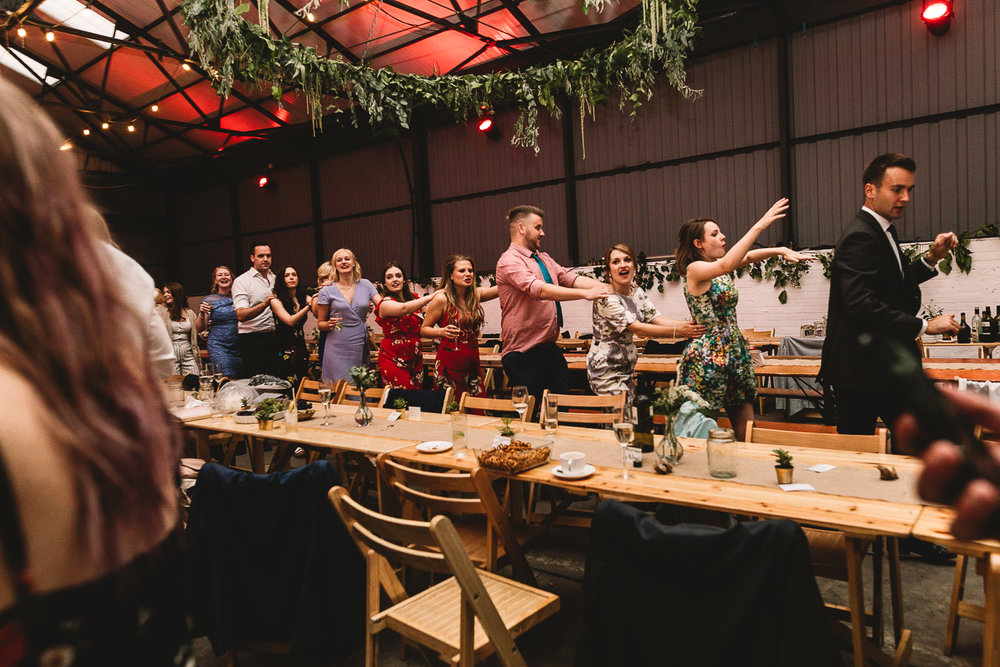 Photo of guests having fun doing the conga around rustic tables in warehouse wedding venue 92 burton road in Sheffield