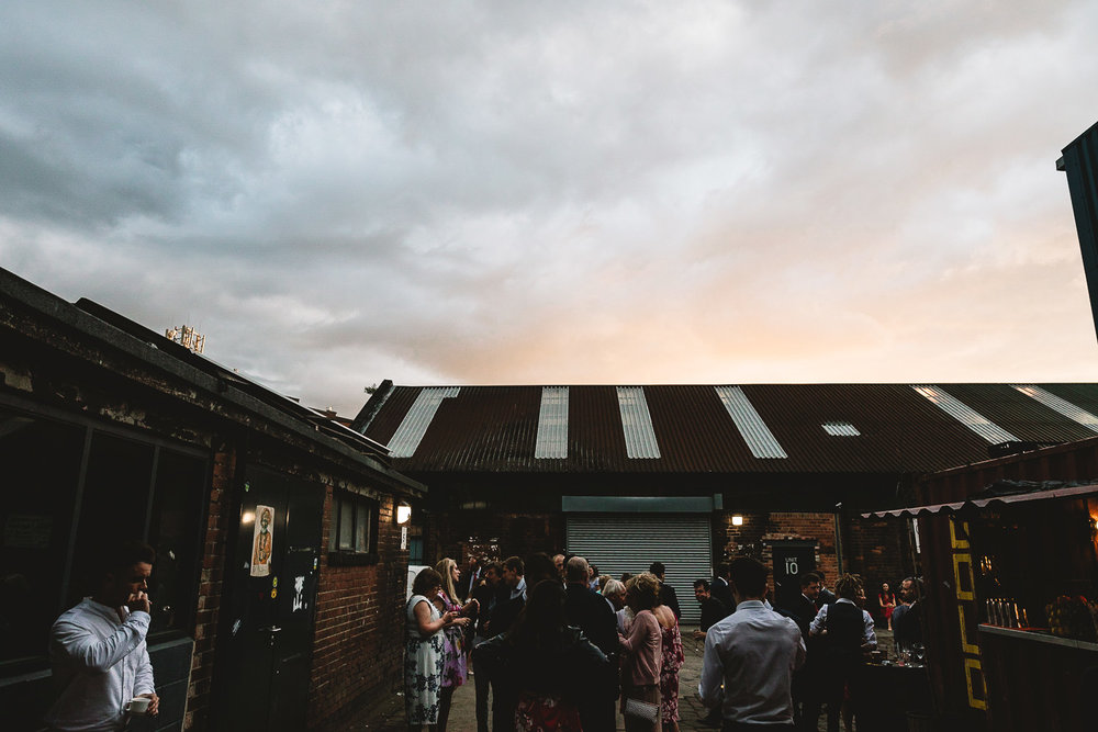 Photo of pink sunset over warehouse buildings at 92 burton road wedding venue with guests stood outside chatting