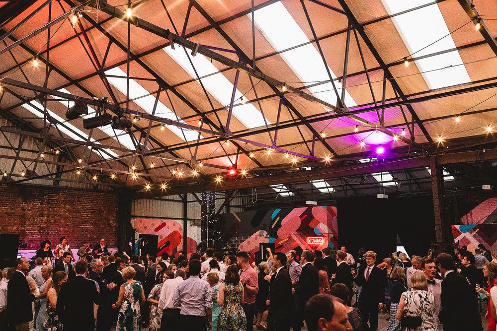 Wide photo of the dance floor flowing full of guests having fun dancing in warehouse wedding venue 92 Burton Road in Sheffield