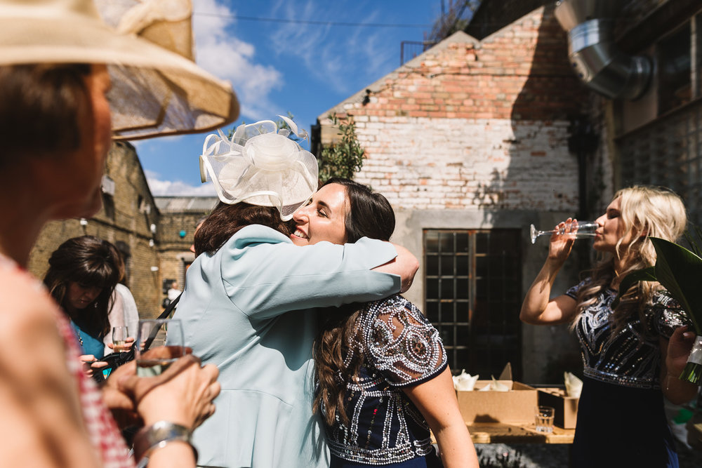 Guest hugging bridesmaid on sunny London day outside of Clapton Country Club