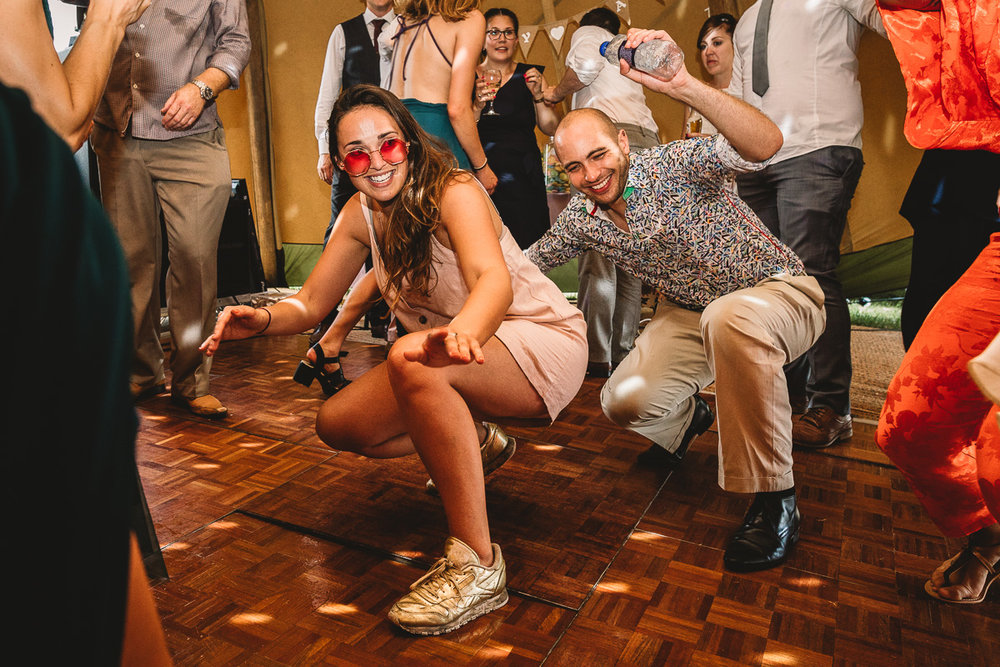 Fun wedding guests dancing on the floor inside of a tipi at festival wedding in Shropshire