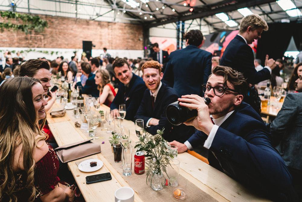 Fun wedding guest drinking from beer bottle at 92 burton road warehouse wedding