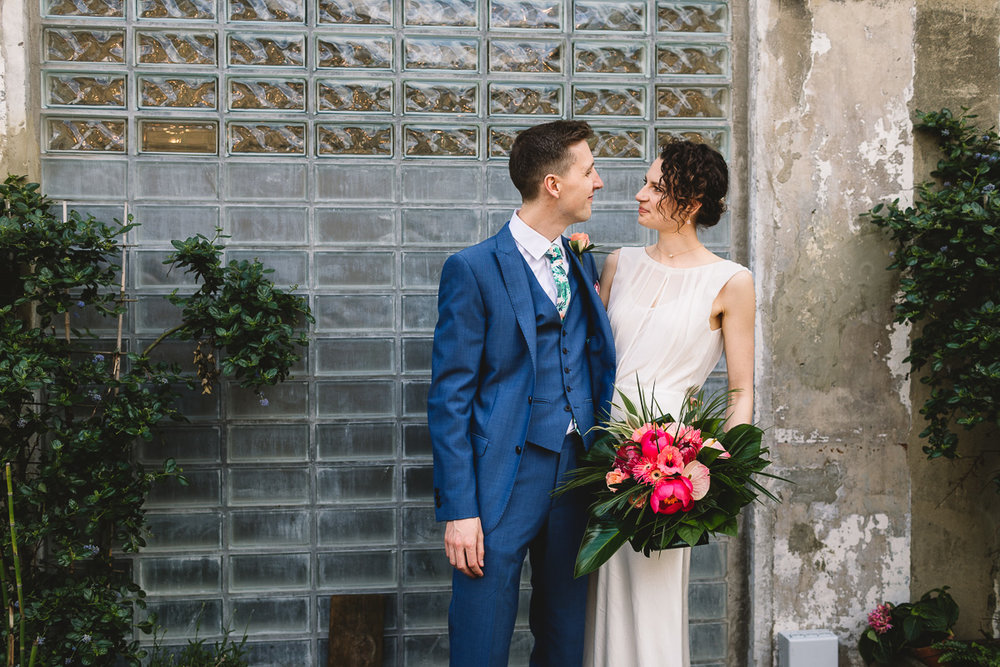 Bride with tropical pink flowers stood with groom in blue suit with tropical tie against glasswork and brickwork outside of London wedding venue Clapton Country Club