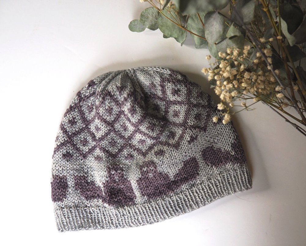 Beaver Hat - This simple beanie shape is worked in a two-color stranded pattern that represent a beaver family and their dam. The hat is available in two sizes: Adult and Baby so you can knit your own beaver family and gift this special hat to your loved ones!