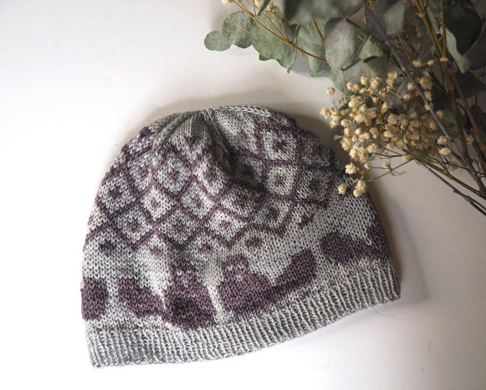 Beaver Hat - Ce bonnet à la forme simple est tricoté avec un motif en jacquard à deux couleurs qui représente une famille castor et leur barrage. Le bonnet est disponible en deux tailles : Adulte et Bébé pour que vous puissiez tricoter votre propre famille castor et offrir ce beau cadeau aux gens que vous aimez !