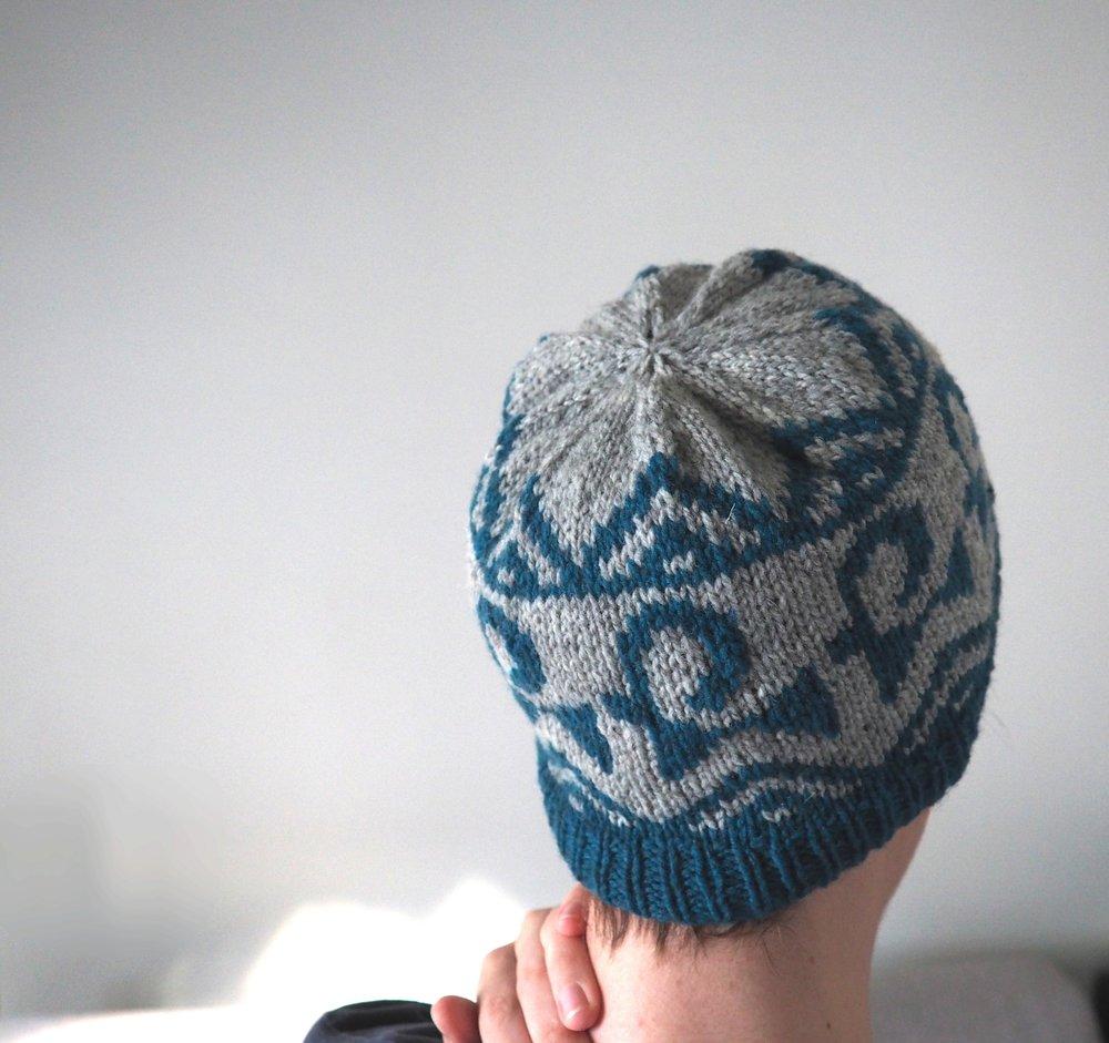 Ibex Hat - Ce bonnet est fait d'un motif de jacquard à deux couleurs inspiré par un motif de bouquetin trouvé sur des vases antiques orientaux. Avec sa forme simple et confortable, c'est le bonnet parfait à porter tous les jours et pour aller se promener dans la nature.