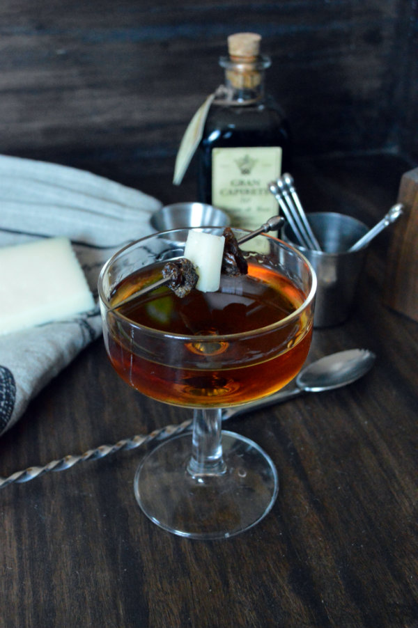 The Andalucia Cocktail using cream sherry, nocello, and shery vinegar garnished with a wedge of manchego | CaretoPair.com