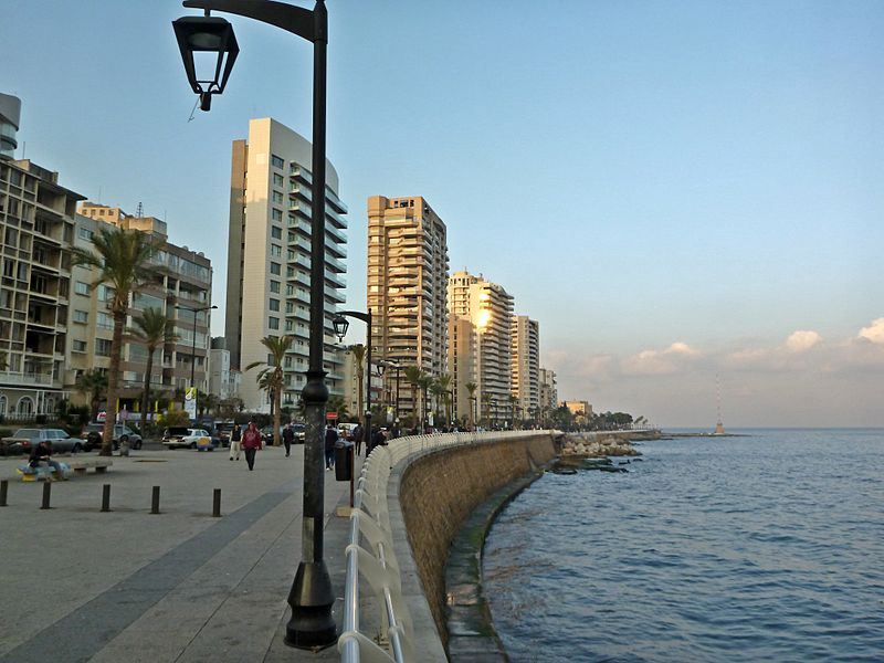 THE CORNICHE   PUBLIC SPACE   EL-MANARA   Stretching from the Ramlet al Bayda area to the Saint George marina, the Corniche is the most renowned seaside promenade in Beirut. Coated with palm trees, it offers a great view of the Mediterranean Sea, as well as some of the country's best assets, namely the infamous Pigeon Rock, and the summits of Mount Lebanon on the eastern side. To the north of Pigeon Rock, you can spot the old Ferris Wheel, still active to this day. Built during the time of the French Mandate of Syria and Lebanon, the Corniche has its origins in the Avenue des Francais, also known as the Ave de Paris, and was constructed along the Beirut waterfront. A testament to the history they have gone through and the hardships they have survived, the trunks of the trees along the Corniche carry bullet holes from the time of the Lebanese Civil War.  Apart from being a great exercising spot (locals from all age groups can often be seen walking, running, cycling, and skating alongside the Corniche), it is also a great pole fishing spot. Old fishermen are often seen along the rails, or down below on the rocks, their fishing poles in one hand, their baskets on the side, sometimes alone, but most times gathered in groups talking amongst themselves. Additionally, families, couples, and groups of youngsters dressed up in their best attire can most always be seen sauntering alongside the length of the Corniche, oftentimes stopping to have a coffee and narguileh break in one the many cafes.   Operating Hours:  24H