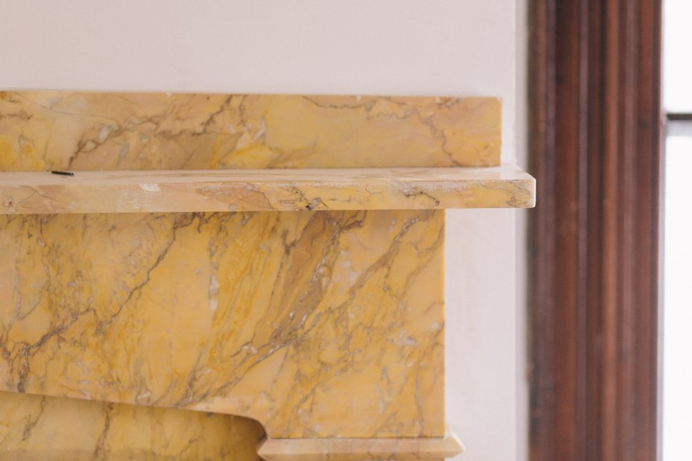 Close up of yellow mantel in first of two Gathering Rooms